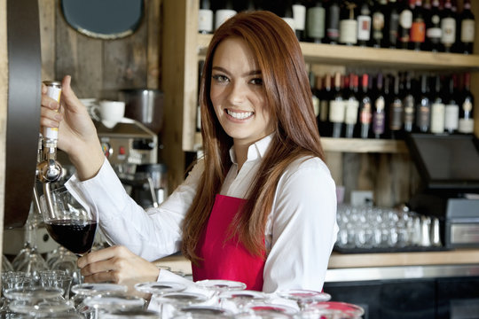 Portrait of a beautiful young waitress removing wine in bar