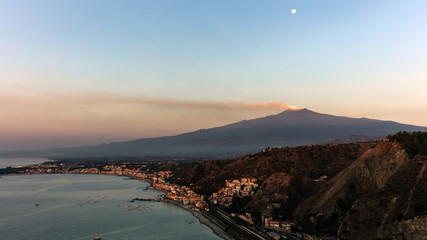 Mount Etna and the Giardini Naxos coastline at dawn. View from Taormina, Sicily, Italy.