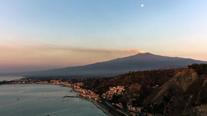 Mount Etna and the Giardini Naxos coastline at dawn. View from Taormina, Sicily, Italy.