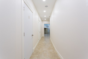 White hallway with doors in a fresh painted building.