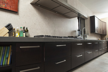 Interior of empty commercial kitchen with drawers and vent