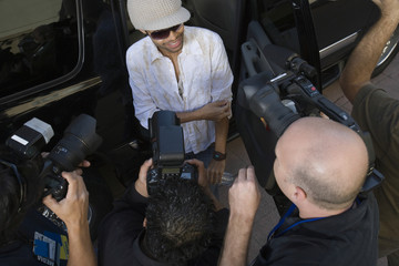 Elevated view of a male celebrity being interviewed by paparazzi