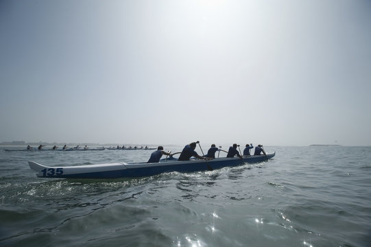 Group of multiethnic people paddling outrigger canoes in race