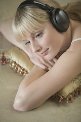 Closeup of thoughtful young woman listening to music through headphones while resting on cushion at home