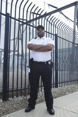 Confident security guard standing with arms crossed in front of the prison fence