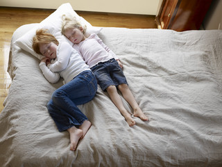 Elevated view of two little sisters sleeping in bed at home