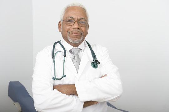 Portrait of an African American confident male doctor standing with hands folded in clinic