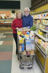 Portrait of a smiling senior couple food shopping in supermarket