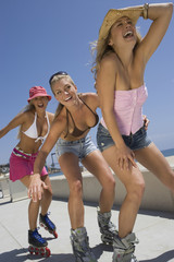 Low angle view of three happy young women on in-line skates