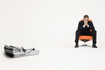 Wad of cash on mouse trap with pensive businessman on chair representing financial difficulties
