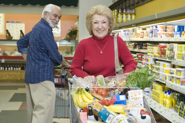Smiling senior couple food shopping in supermarket