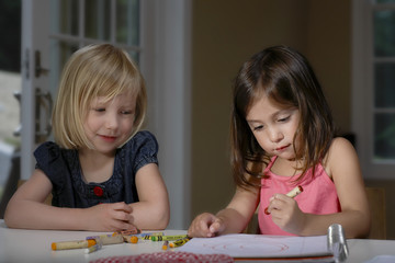 Closeup of two young girls drawing with crayons in book