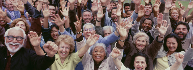 Large group of multi-ethnic people cheering with arms raised
