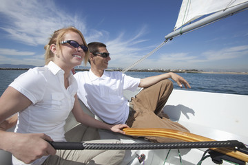 Deurstickers Zeilen Happy couple relaxing together on deck of sailboat