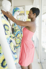 Side view of an African American female shop assistant dressing mannequin in clothes store