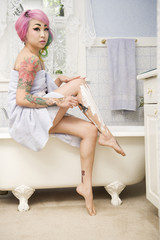Woman shaving her legs on the side of the bathtub