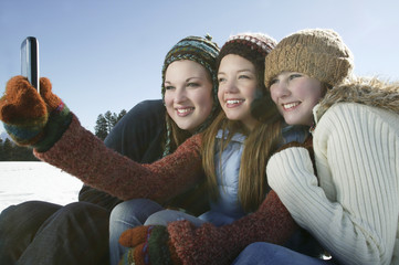 Three female friends taking self portrait through cell phone in winter
