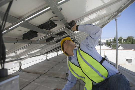 Young maintenance worker adjusting solar panels on rooftop