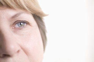 Closeup of senior woman with gray eye over white background