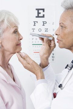 Senior female doctor checking patient's eye using testing instrument in clinic
