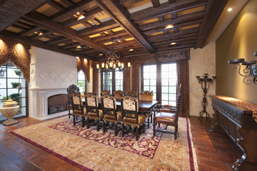 Chandelier hangs over dining table from wood beamed ceiling