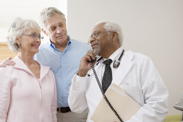 An African American senior male doctor looking at patients while using landline phone