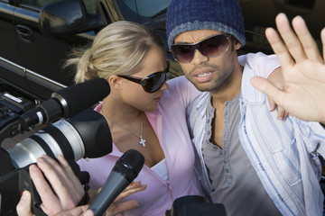Closeup of celebrity couple and paparazzi