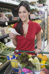 Portrait of a smiling young woman with shopping in supermarket