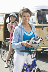 Portrait of happy mother and daughter ready to go for cycle ride with campervan in background