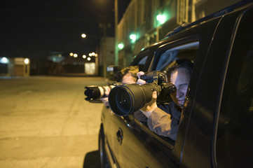 Professional photographers with telephoto lens in car