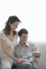Happy mother and father with their newborn baby at home