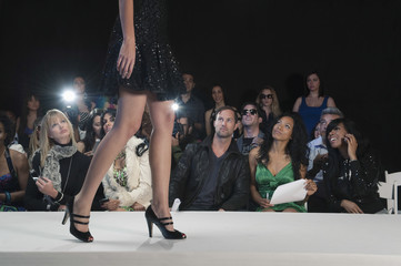 Spectators watching a model walk in black high heeled shoes