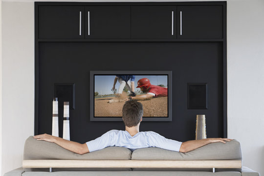 Back view of mid-adult man watching baseball game on television in living room