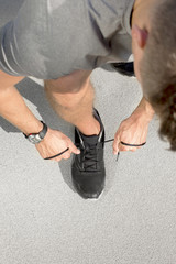 High angle view of sporty man tying shoelace on street