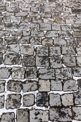 grey granite city road surface pattern with white snow and ice