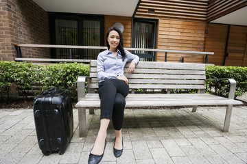 Full length of confident businesswoman sitting on bench by luggage against building
