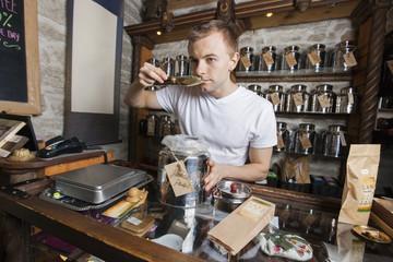 Salesman smelling tea in store