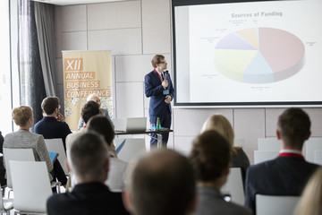 Businessman explaining pie chart to audience in seminar hall
