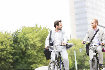 Businessmen talking while riding bicycles outdoors