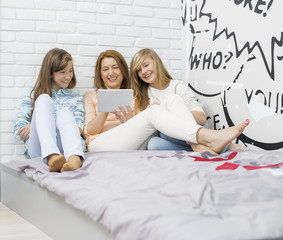 Mother with daughters using digital tablet in bedroom