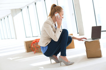 Side view of young businesswoman crouching while using mobile phone and laptop in new office