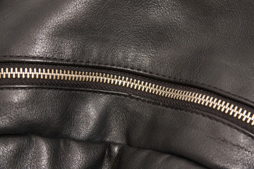 A zipper on the black backpack.