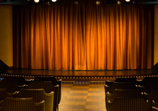 Small stage with orange curtains in cameral private cinema