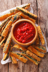 Fried slices of zucchini with parmesan cheese and breading and tomato sauce closeup on a table. vertical top view