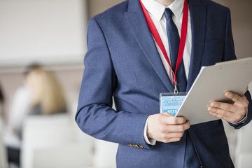 Midsection of businessman holding clipboard in seminar hall