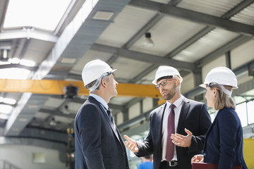 Business people wearing hardhats having discussion in metal industry