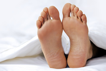 Person's foot in bed, close-up