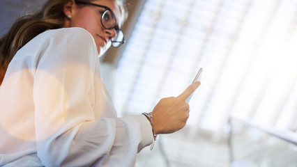 Bottom view. Young business woman in glasses and a white shirt, standing in room and use smartphone. Girl holding in hand mobile phone. Female uses digital gadget. Selective focus, bokeh effect.