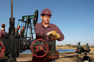 Two Oil Workers Repair an Oil Well at Oilfield / Two workers repairing a oil pumping unit at oil well construction site