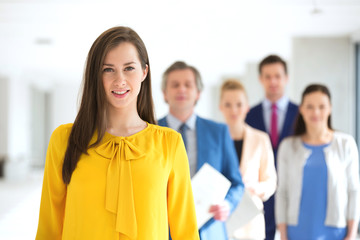 Portrait of smiling young businesswoman with team in background at office